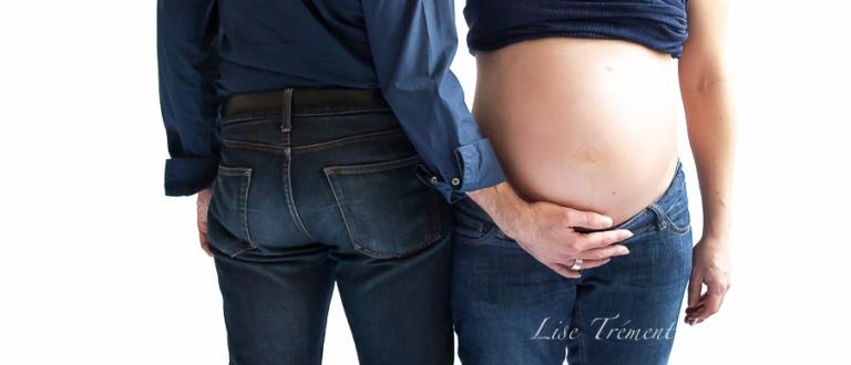 C'est une photo d'une jeune femme enceinte, ventre nu, face à la photographe, le papa, dos à la photographe a sa main posée sur le votre arrondi de sa femme.